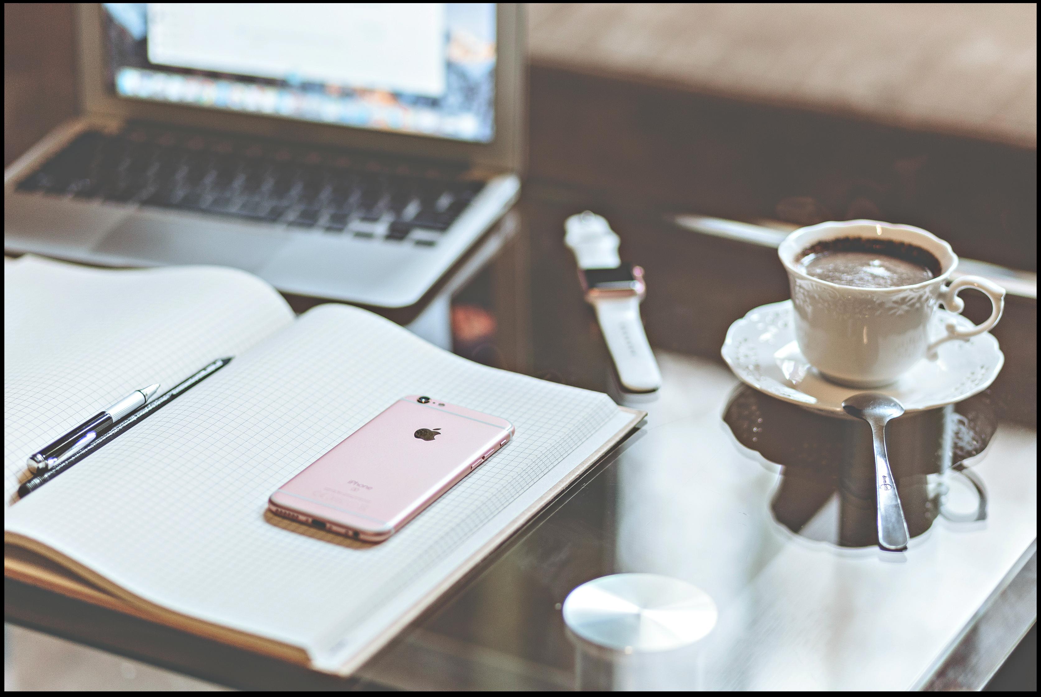 Desktop with laptop computer, open journal, pen, iPhone, cup of coffee