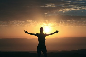 Person feeling gratitude looking at the sunrise with extended arms