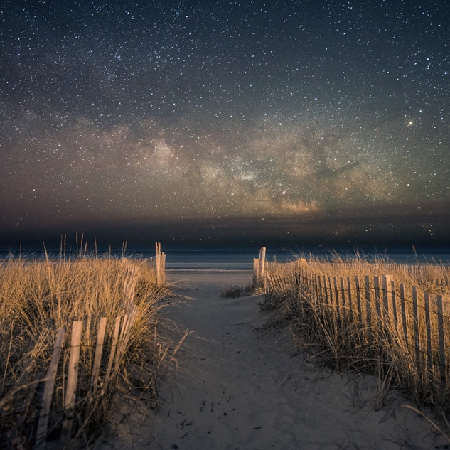 Beach at night with starry skies over ocean