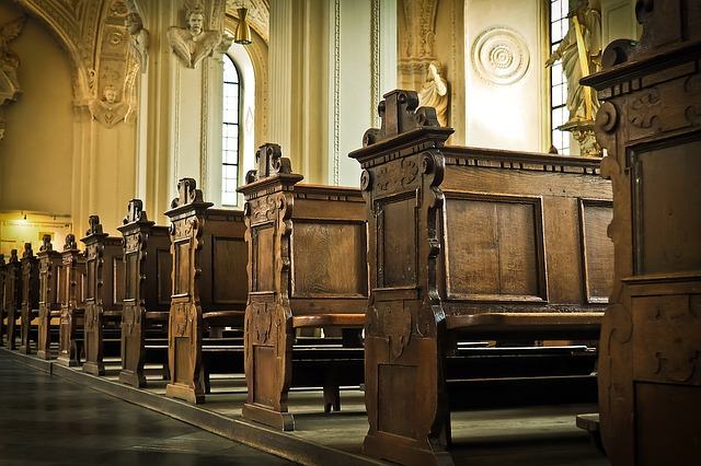 A row of ornate brown wooden church pews