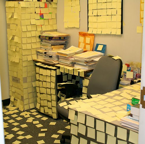 Office with yellow sticky notes on every surface.