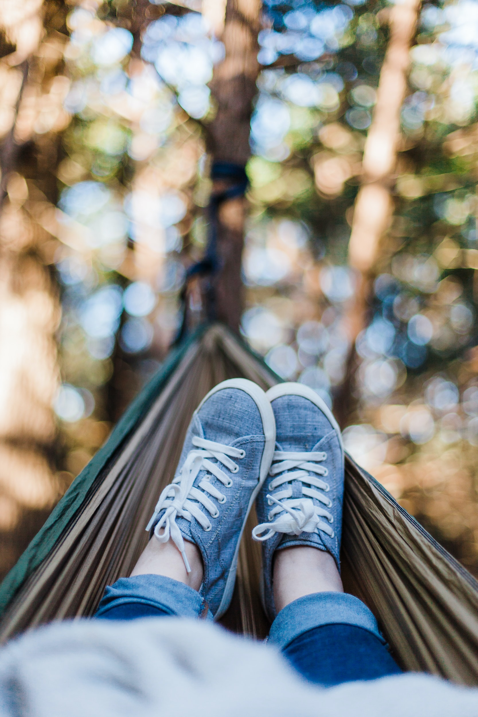 A pair of feet in relaxation mode at the end of hammock surrounded by trees.