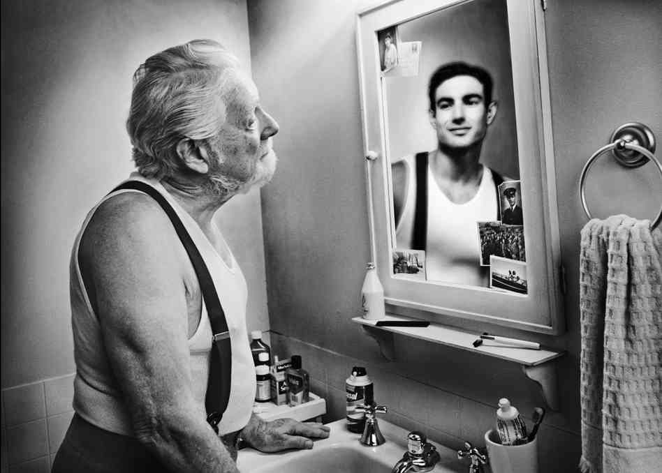 Old man looking in mirror at his younger self